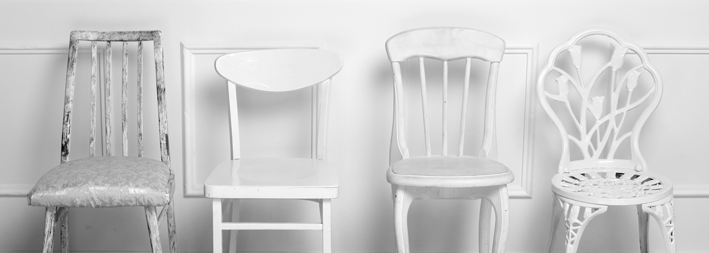 Photo of waiting area, of vintage chairs lined up against the wall.
