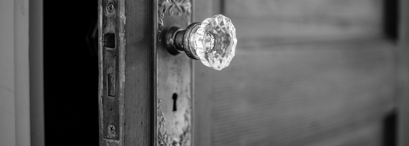 Photo of a rustic door, slightly ajar, with vintage handle.