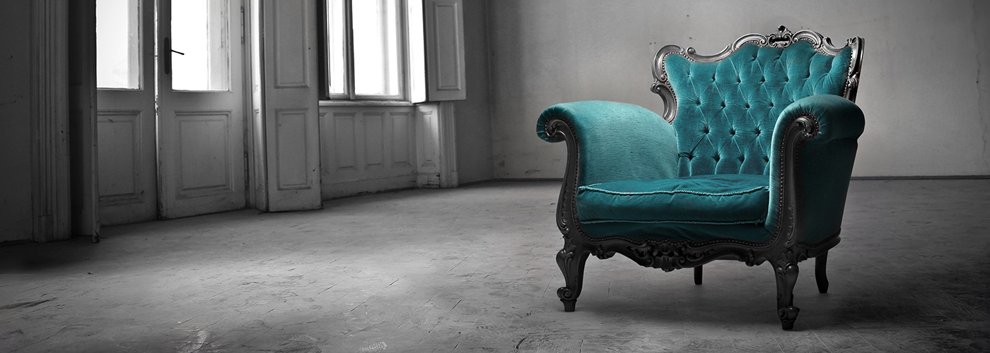 Image of a tufted chair in an empty room.